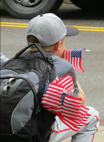 A child handing out flags alongside Beaver Avenue on September 11th, 2016 to remember the fallen hereos from 9/11.