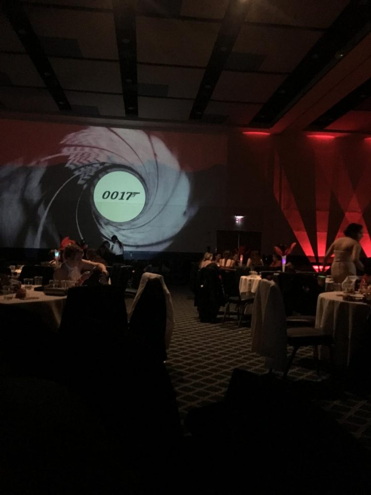Projection screen and tables decorated at Senior Prom with the theme 0017.