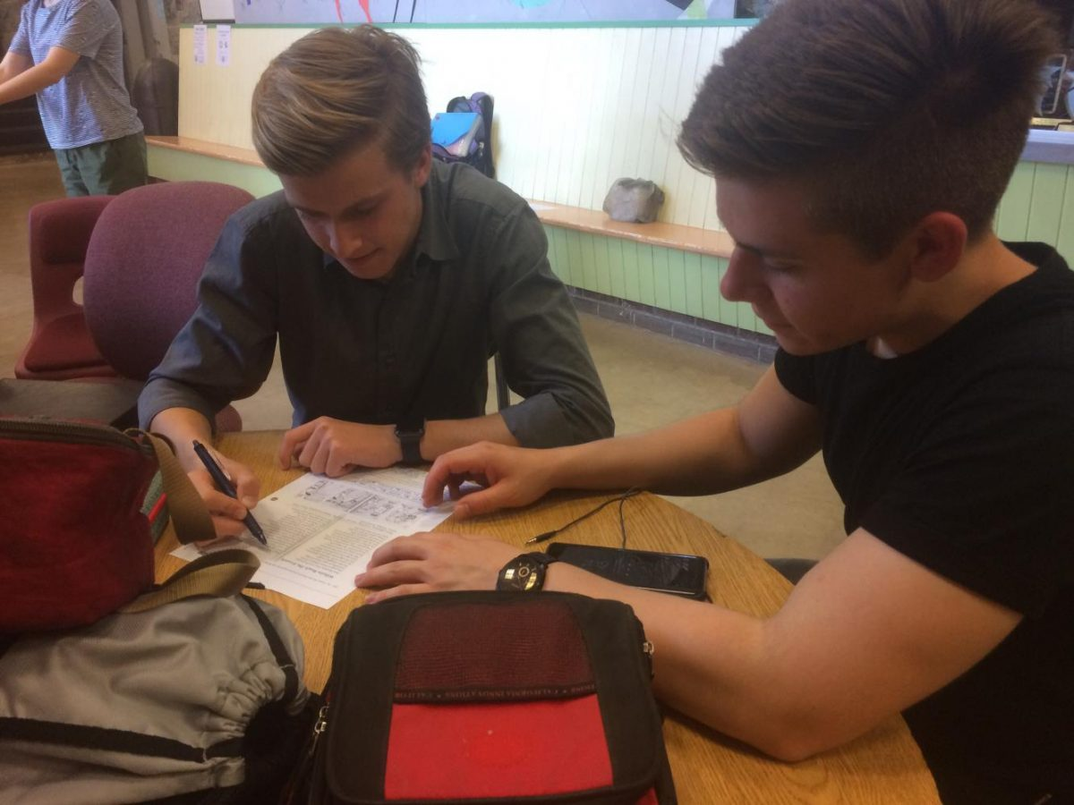 """German exchange student Tim Gad and the senior hosting him, Daniel Cullin, look over homework during study hall. The German exchange students were at State High from September 18th to October 4th and attended classes with their hosts. """"For a few weeks, it's like having a sibling, a twin sibling, where they're doing everything you're doing and with you almost all the time. It's really cool because you always have someone you can bounce ideas off of and make jokes with,"""" Cullin said."""