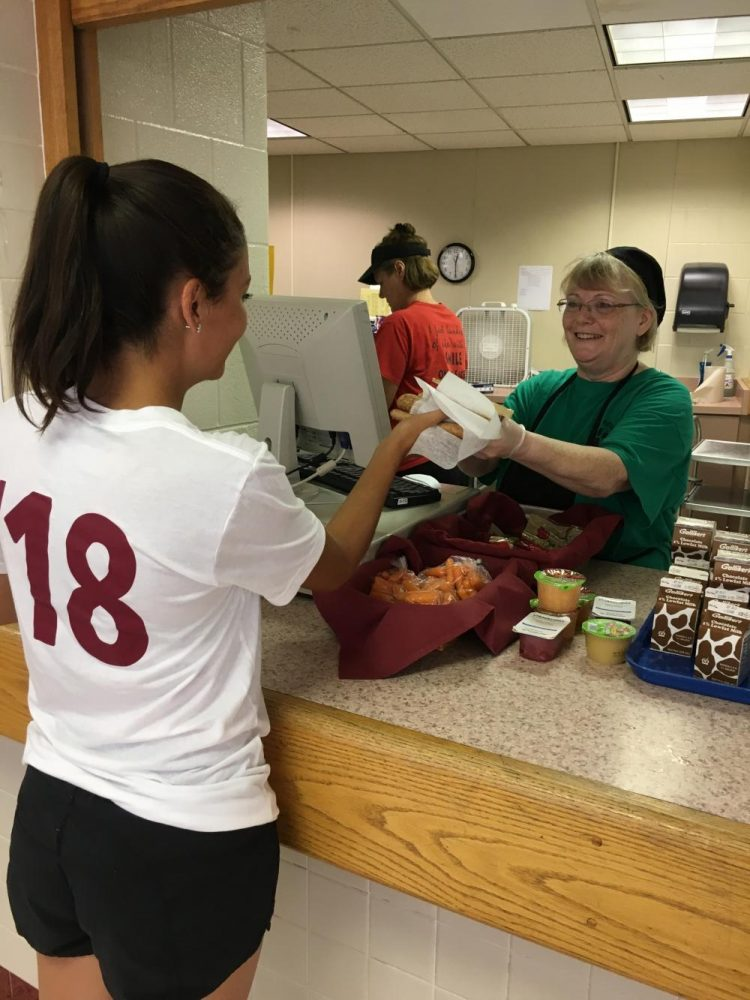 Senior Sydney Asencio receiving her slice of pizza from cafeteria employee Anna Ireland.