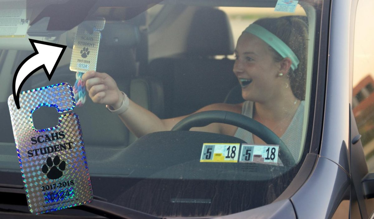 Senior Lily Dochat adjusts her full year parking permit with a smile.