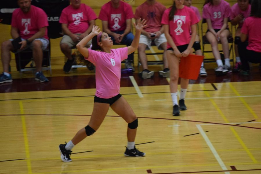 "Freshman Ariana Angus serves the ball during the girls' volleyball Pink Out. The team held the Pink Out in honor of breast cancer awareness month. The team has worked cohesively to help the thirteen freshman this season. ""I've learned a lot from the upperclassmen this year, and it's very beneficial to have them as mentors because it makes things easier and I am able to learn a lot from them,"" said Angus."