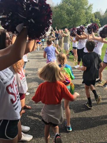 Corl Street students begin the run while State High's cheerleaders encourage them.