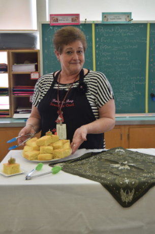 Mrs. Judy in her classroom in the State High North building displaying a side dish prepared for a class cooking lab.