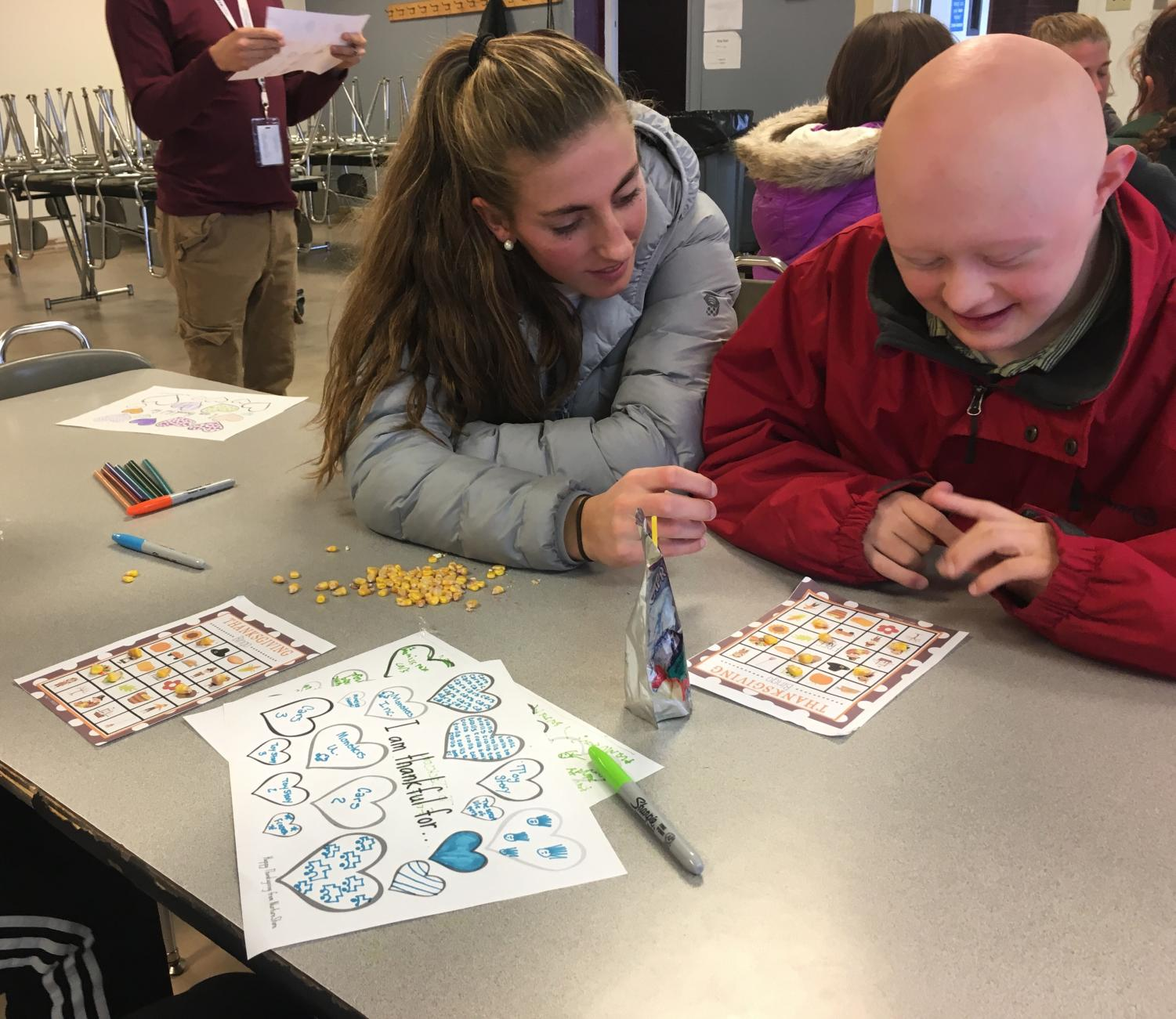 "Seniors, Esther Seeland and Sam Moyer, enjoy each other's company while playing Thanksgiving-themed bingo. Esther said Best Buddies is a, ""a great experience and you get to know people you don't normally spend a lot of time around."" Best Buddies continues to provide a welcoming environment for all students to make new friends and have fun!"