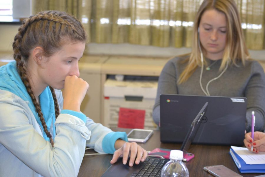 Ashley Franks, sophomore and Lily Dochat, senior, working hard in their study hall to complete their final assignments for the first marking period.