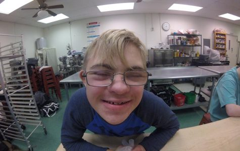 """Jackson Lippincott, freshman, shows a big smile during the cooking of Thanksgiving dinner. """"I had so much fun doing this,"""" Lippincott said. The Wild Dream Team spent a day right before break preparing a Thanksgiving meal. The meal was prepared for kids who would not be able to have a Thanksgiving dinner provided for them."""
