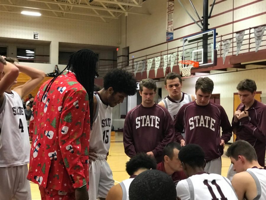 "State High Boys Basketball players convene during the Silent Night game to discuss in-game adjustments. ""Our focus and ball movement was great"", said senior Brandon Clark (15). The win added to the team's five game winning streak."