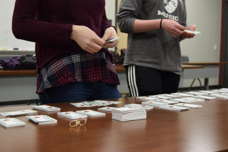 Sophomore Mikayla Martin and junior Kathryn Salada sort crisis cards.