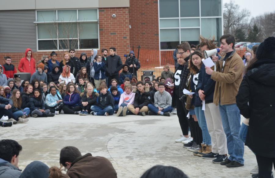"Seventeen speakers stand at the front of the large crowd outside of SCAHS.  ""I chose to speak because it's important to me, both as a student and a budding activist to make my voice heard,"" said sophomore Kyra Gines."