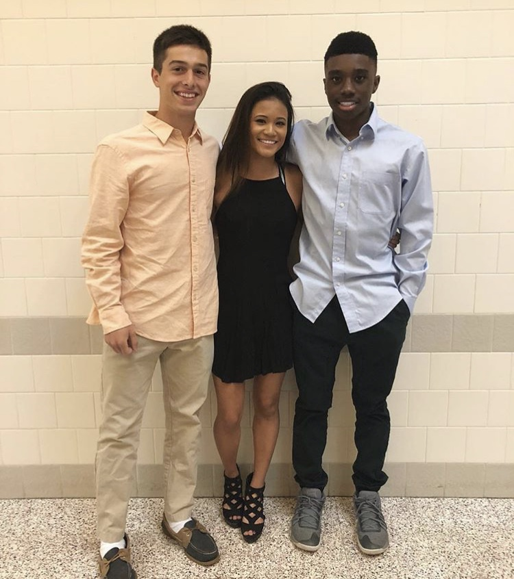 """On April 28, 2018, Froshmore took place at Mount Nittany Middle School. Sophomores Zach Decarmine and Lokey Howell and senior Lily Plute pose for the camera before rocking the dance floor. """"I went because it was the last school dance that I could have gone to other than prom. I will miss school dances because it was always fun to put on dresses and dance,"""" Plute said."""