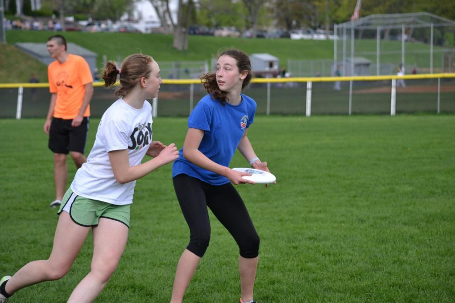 "Nyra Graham and Maddie King, freshmen, play in an ultimate frisbee scrimmage at Community Fields. ""My favorite part of ultimate is the atmosphere of the club. I love how supportive the team is and how scrimmages can be competitive and exhilarating,"" said Nina Burgos, sophomore. The co-ed ultimate frisbee team is a great way to exercise and spend time with friends. Photo by Alex Voight- Shelley."