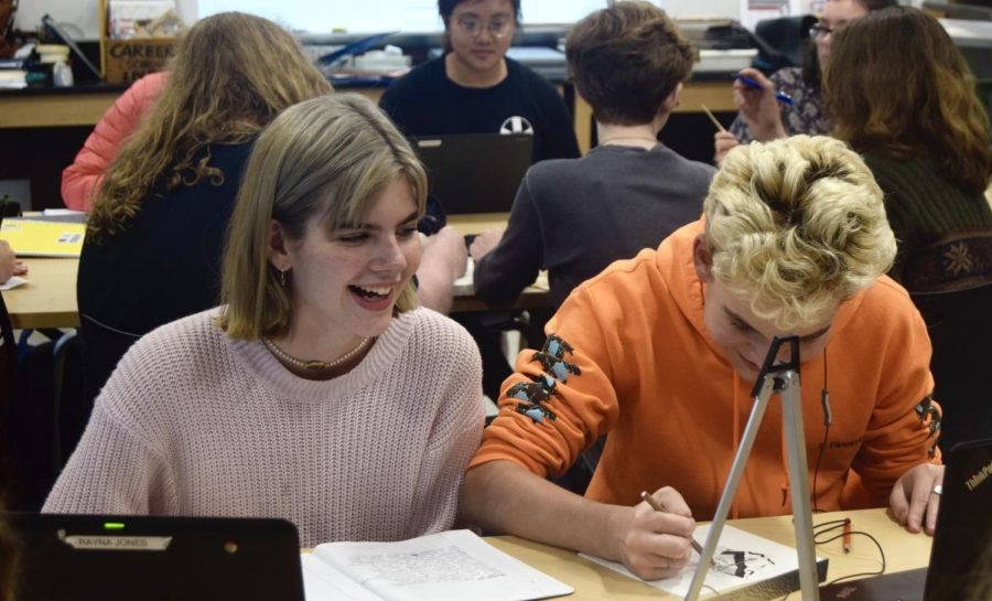 Rayna Jones and Martin, Switalski, juniors, laugh while working on their art projects in Art Club.