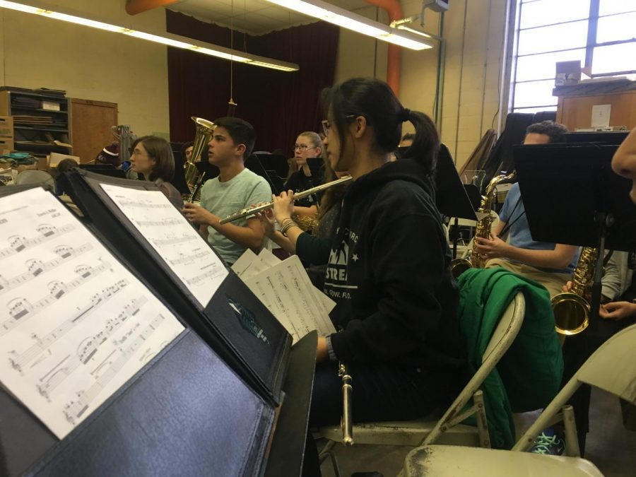 "Students in symphonic band sit in the old State High Auto Shop, currently used as the band and orchestra room.  After winter break, music students will be moving into the South Building library until the music wing is complete. ""As long as the location benefits the sound of the band, I think it will be good."" said sophomore Dorothy Tan. (Photo courtesy of Ella Simpson)"