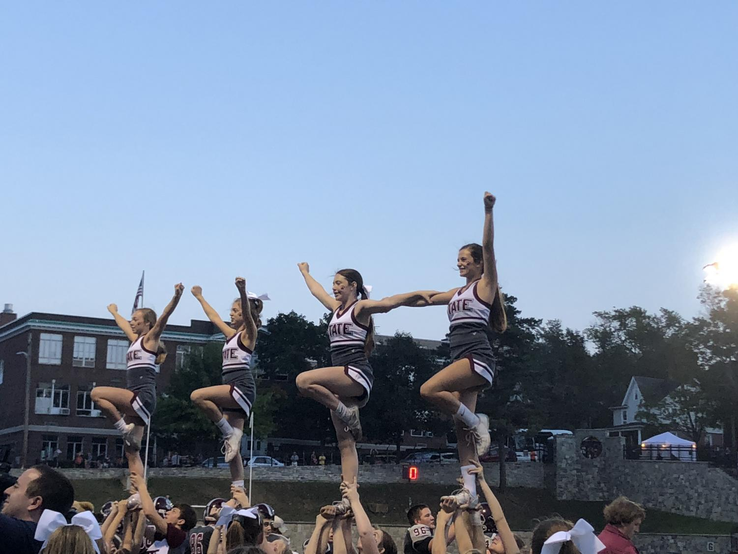 "Four varsity cheerleaders, flyers on the team, are lifted into the air during one of their cheer routines at the 2018 State High Homecoming football game. Rylie Grube, varsity cheerleader, said, "" I love football season and getting the chance to watch the game on the field with my team."""