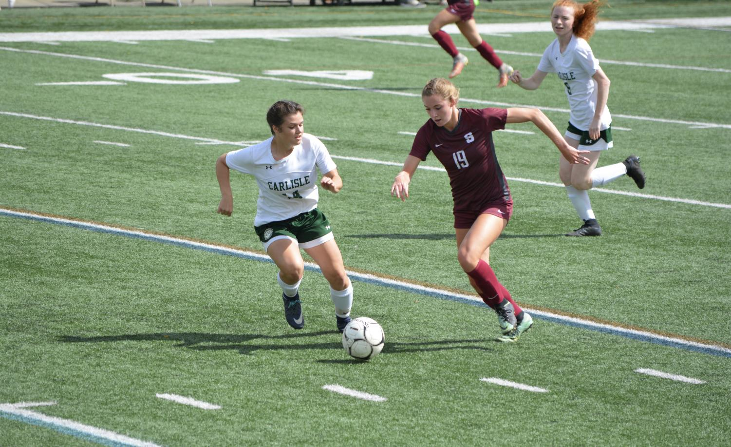 """Erica Feese(right),senior, #19, breaks away to score her second of four goals in the game. """"Even though we let two goals in early, we didn't give up and rallied for the 6-4 win,"""" Feese said."""