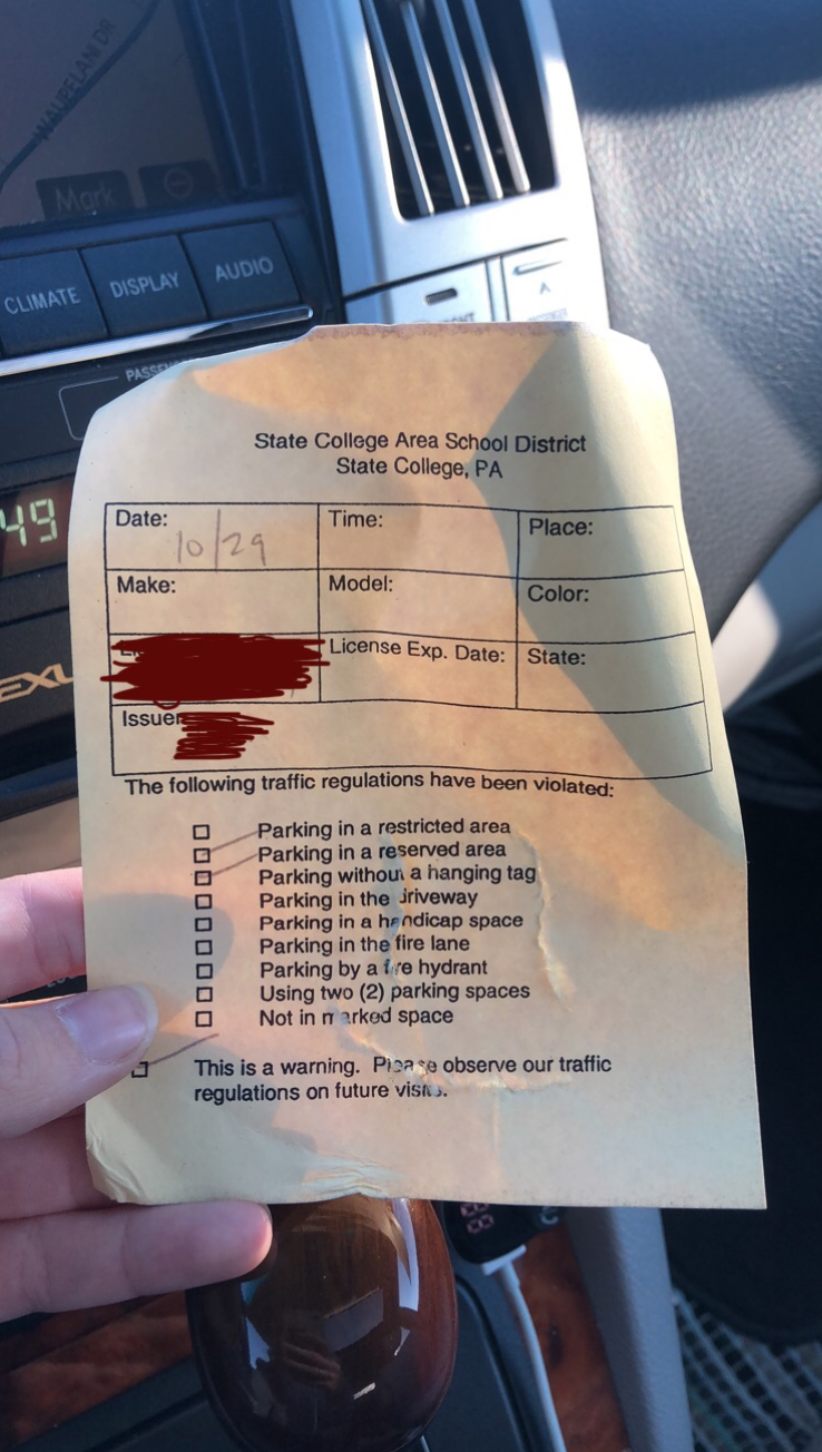 "Students received the pictured warning on October 29th on their car windshields. The violated regulations were cited as ""parking in a restricted area"" and ""parking in a reserved area"". Many student drivers plan to find a new parking spot, but are currently in search of temporary homes."