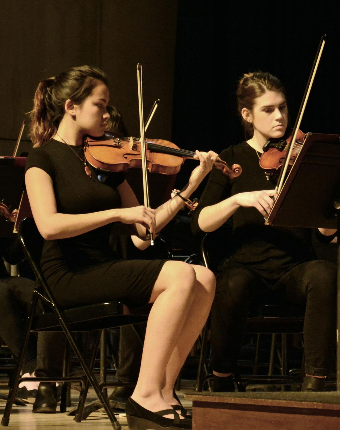 """First violinist, Maria Bressan (pictured on the left), plays her violin during the winter orchestra concert on December 10th. Bressan details why she loves playing the violin. """"I think the violin has the greatest range of color out of all instruments, so it gives the players a lot of freedom of expression."""""""