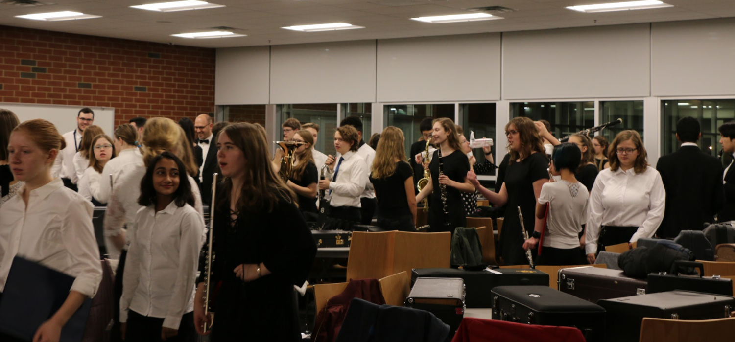 """The State High Band prepares and warms up for their annual winter concert. For many, the concert's occurrence is synopsis to a Christmas gift. """"Playing music along with many talented individuals is one of my favorite things to do, and I love showcasing our art at the winter concert,"""" junior Selena Kesidis, a member of the band, said."""