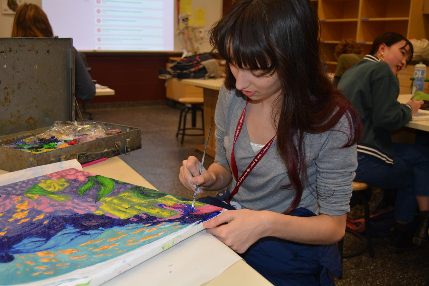 """Madeline Einfalt, junior, works on a painting during her master studio class in the new art space. Einfalt shares a reason why she likes the new rooms. """"I like the space the new rooms have,"""" Einfalt said."""