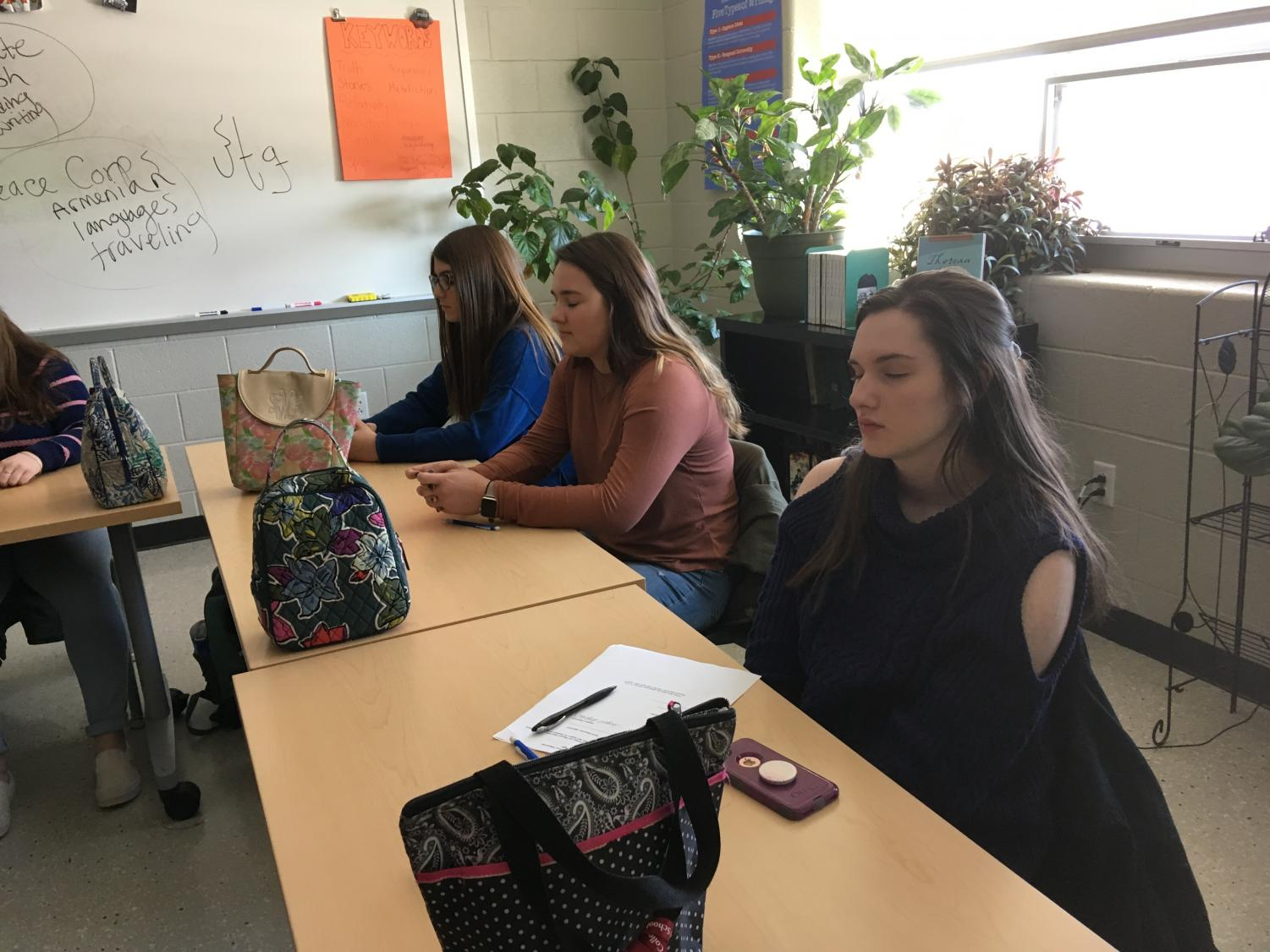 "From right to left, juniors Caylee Thompson, Taylor Balboni, and Lily Maxwell practice mindfulness during an English class. Mindfulness can be used in class or life to reduce levels of anxiety and stress. ""I like that it gives us time to prepare before class and relax,"" said Thompson."