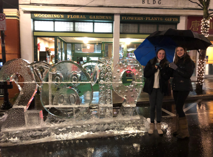 "Freshman Maggie Bopp and Sophomore Hadley Crownover, pose  in front of 2019 ice sculpture at First Night. They enjoyed looking at the different ice sculptures Downtown. ""It was unfortunate that it was raining, but it was still fun to see the different ice sculptures with my friends,""  Crownover said."