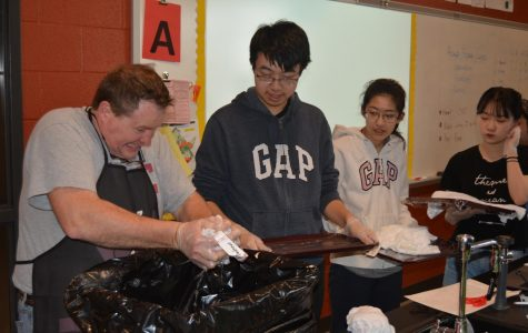 "ESL students wait in line to prepare their t-shirts to tie dye. ""Ugh...""  Mr. Wilson said while squeezing Andrew's t-shirt."
