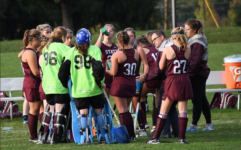 """The JV team huddles up to discuss gameplay. Mink, pictured right, coaches the team alongside JV coach Meily. """"To be effective, I need to turn concept into action. It's one thing to say you're going to do something, but to actually do it, is where the growth happens,"""" Mink explained."""