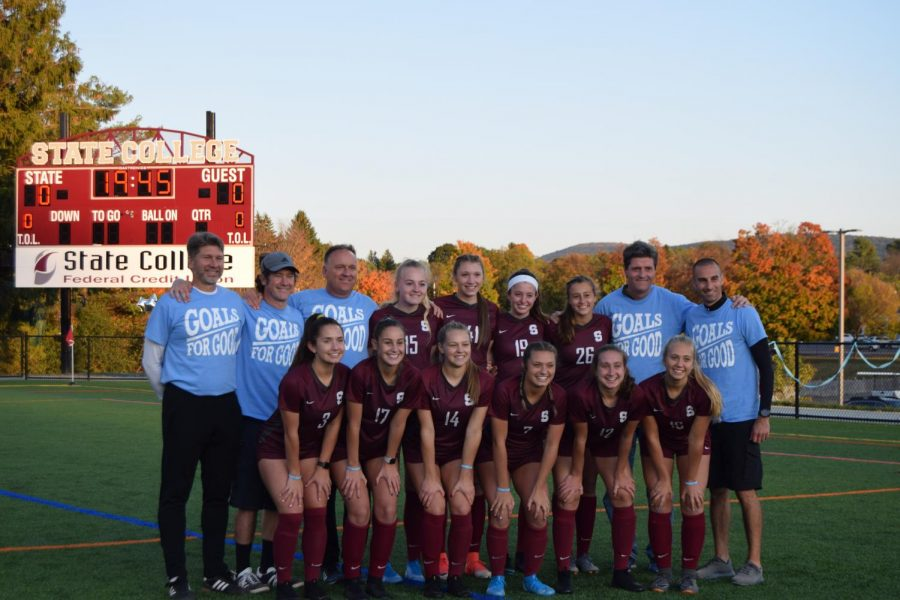 """Girls soccer seniors pose for a photo with their coaches. """"Senior night is very important to me because we get to celebrate our senior class who has been through so much together. It's special to celebrate our group as a whole and play for each other,"""" senior Savannah Schoonmaker said."""