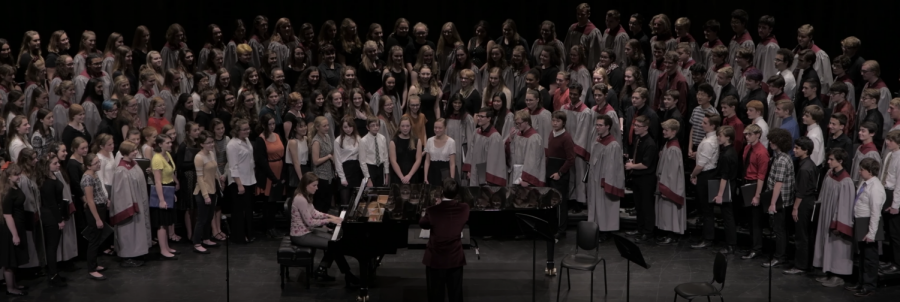 All+choirs+smile+after+receiving+a+look+of+pride+from+director+Erik+Clayton+after+their+combined+performance+of+%E2%80%9CAve+Verum%E2%80%9D+by+W.A.+Mozart.+This+is+a+song+that+Clayton+loves+the+choirs+to+perform+together+and+they+performed+it+at+the+dedication+ceremony+earlier+this+year.+%E2%80%9CHearing+the+different+dynamics+with+everyone+on+stage+is+so+interesting+and+hearing+so+many+people+in+the+different+parts+was+so+cool%2C%E2%80%9D+Jaqueline+Lawrence%2C+sophomore%2C+said.+