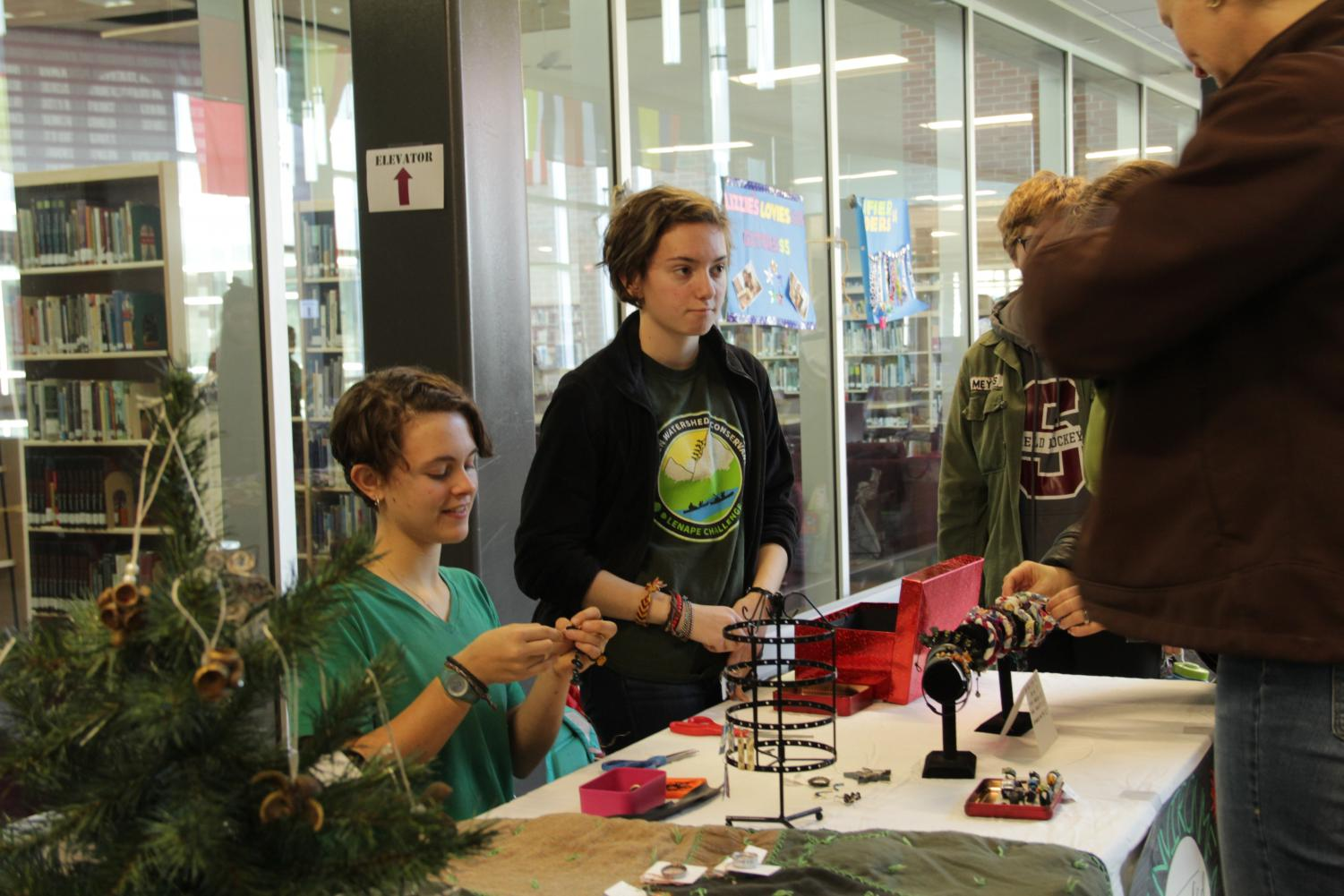 """Sophomores Lucinda Kaye and Caitlin Moser from the Environmental Club participate in the Holiday Bazaar. The Environmental Club sold jewelry and ornaments made out of recycled material at the Holiday Bazaar. """"We were selling things made out of recycled material because there is a lot of waste associated with the holidays and we wanted to reduce that waste as well as show people that you can make nice gifts out of things that are usually considered trash,"""" Kaye said."""