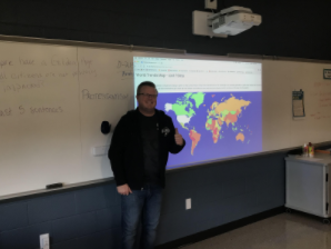 "9th grade World History teacher Mr. Kimbro in front of the Fan Geo countries. ""When we first did Fantasy Geo in class, it felt like a nice break from the usual note-taking routine,"" Nicholas Sloff, a freshman in Mr. Kimbros world history class, said."