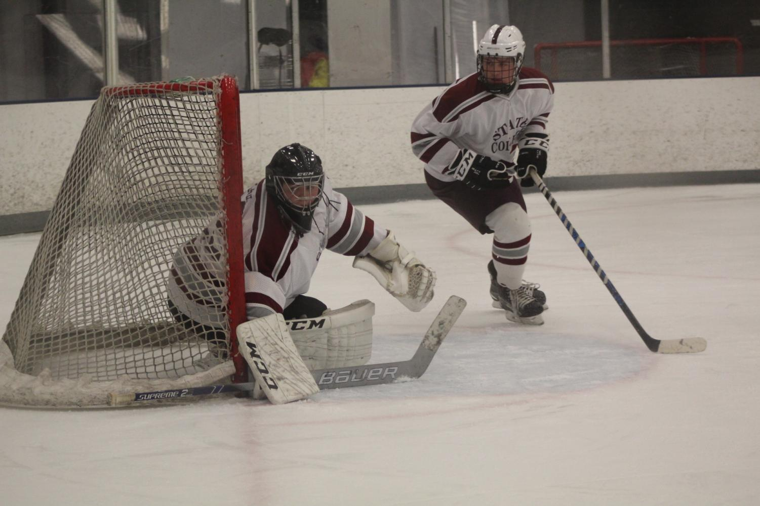 Brothers, sophomore John Olsen (left) and senior Wesley Olsen (right), watch the puck during the State College varsity hockey game against Central Cambria.