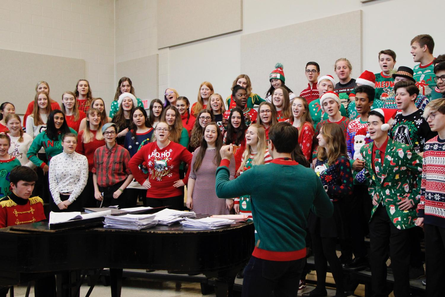 """State High Choirs rehearse Mariah Carey's """"All I Want For Christmas Is You"""" before going on stage to perform. This song featured senior Caylee Thompson, and was popular among both the audience and students.  """"Hearing Caylee sing 'All I Want For Christmas Is You' was so good and she gave me chills,"""" junior Anna Farris said."""