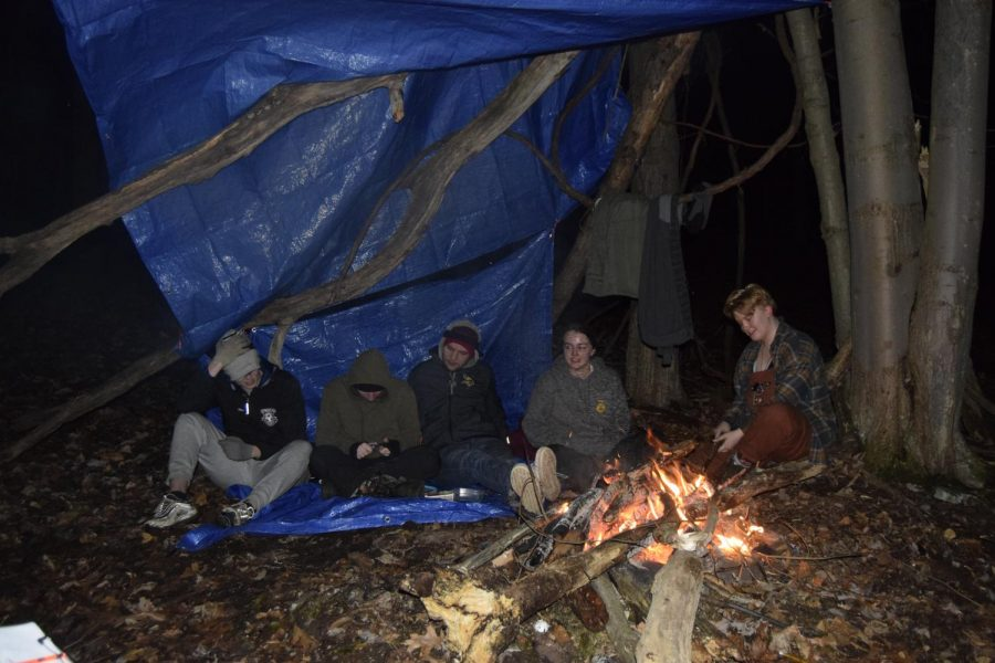 Students on the Survival Science Final Trip relax under their finished shelter after successfully starting a fire.