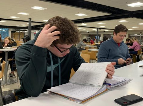 "Ryan Domico, sophomore, studies during his cafeteria study hall. Nationally, students have reported high levels of stress due to school. ""It's kind of 'cool' to be stressed nowadays,"" Merel Padt, senior, said."