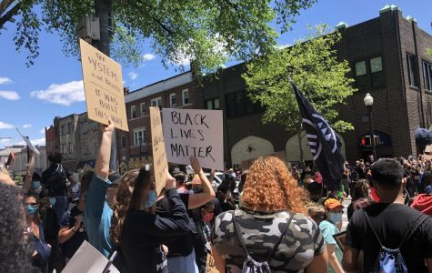 Protesters gather in downtown State College, wearing masks and holding signs. One sign reads