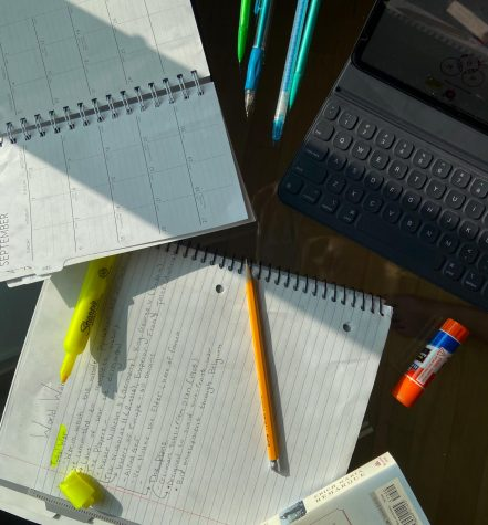 Pencils and highlighters are scattered across a notebook, planner, and desktop. A make-shift workspace for remote learning, Sept. 14, State College.