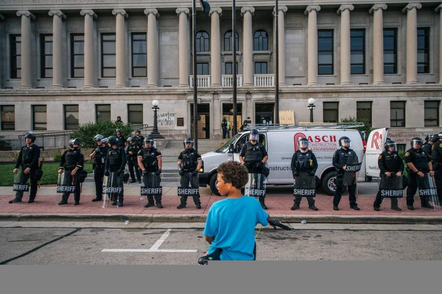 Seated on his bike, a young boy gapes at the long line of law enforcement officers in front of him wearing helmets, riot gear, and shields, standing by the Kenosha Courthouse, WI, on August 24, 2020.