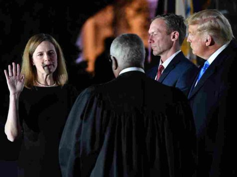 President Trump watches as Amy Coney Barrett is administered the constitutional oath at the White House on Oct. 23, 2020.