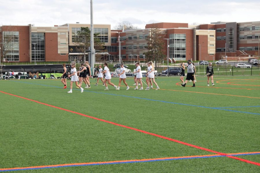 State High Girls' Varsity Lacrosse team players celebrate a goal against Trinity on Tuesday, Apr. 13. The evening games ended in an 18-8 victory for varsity and a 5-2 loss for junior varsity.