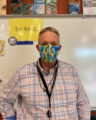 """Andrew Merritt standing in front of a """"Be kind"""" poster in his classroom on Wednesday, Jun. 2. He often repeats that his most important rule in the classroom is simply to be kind."""