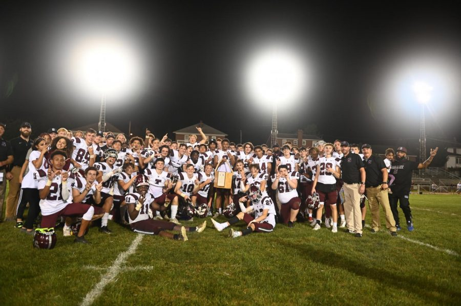 The State High football team poses with the Seven Mountains Bucket Trophy. The trophy is a seven sided bucket, and each side is made from a different wood harvested from the mountain that separates the two schools.